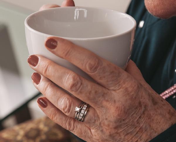 An older woman's hands around a mug